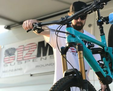 Daniel works on a Yeti mountain bike with an 812 MTB Suspension banner in the background.