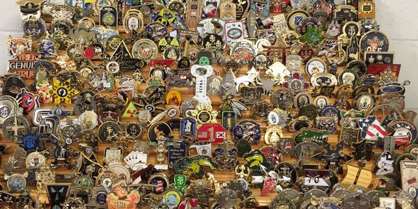 An assortment of challenge coins on a wooden rack.