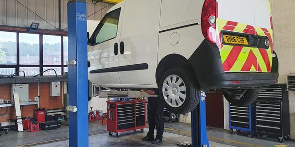 Two post vehicle lift being thoroughly examined