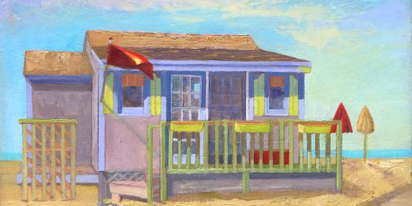 Beach cottage with umbrellas and a red flag