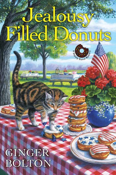 A cat named Deputy Donut squashing a blueberry filled donut on a table decorated for the Fourth of July on the cover of Jealousy Filled Donuts by Ginger Bolton