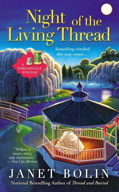 An elaborate wedding skirt in a gazebo in a park in Threadville on a moonlit night on the cover of Night of the Living Thread by Janet Bolin