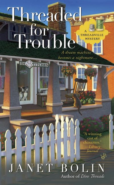 Two dogs looking through the glass door of the machine embroidery shop In Stitches in Threadville. A cat looks back at the dogs on the cover of Threaded for Trouble by Janet Bolin