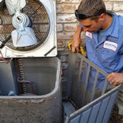 HVAC technician performing maintenance on an air conditioning condenser