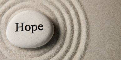 "The word ""hope"" written on a rock and placed on the sand in the middle of five zen circles"