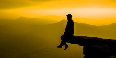 A person sitting on the edge of a mountain cliff, staring out into the sunset horizon