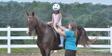 "Instructor helping out the ""Right"" way to ride a horse."