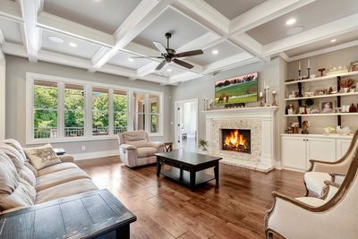 Living room with fireplace, coffered ceiling, crown molding, built-in cabinets, hardwood floors