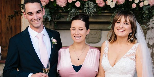 Auckland Wedding Celebrant Yvette Reid posing for photo with happy newlyweds