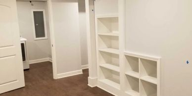 basement remodel with built in book shelves and moulding