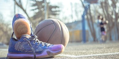 Reboot Sport Defender. Get back on the field. Image of shoes and basketball on outdoor court.
