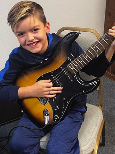 Young student learning to play guitar with a big smile on his face at the Norman Music Institute