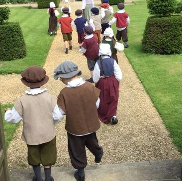 Tudor school children walking into the Manor