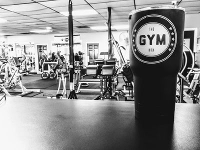 The GYM shaker bottle and interior photo of The GYM in background