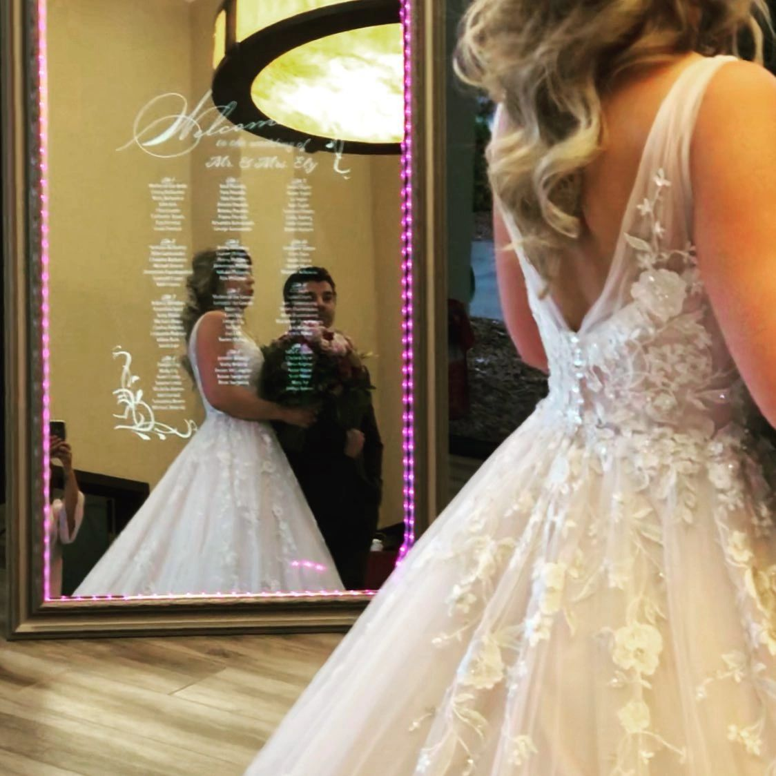 bride interacting with the mirror photo booth as she walks down the aisle to start her new life as 1