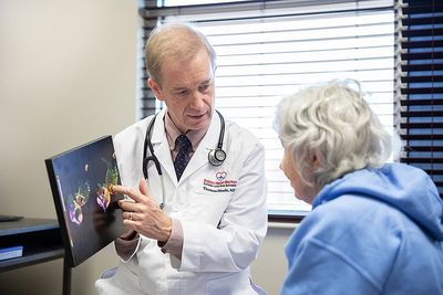 Dr. Thomas Meade describes a heart condition to a patient at the office.