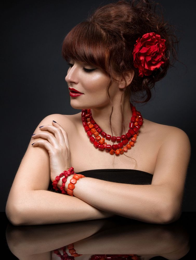 natural coral necklaces, bracelets, and jewelry worn by a model.