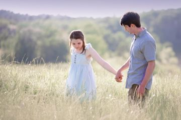 young couple walking through a field holding hands