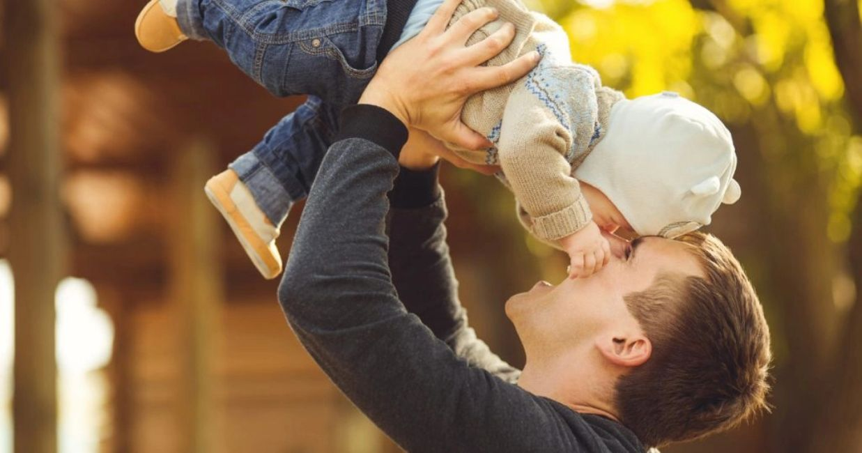 Young father with his infant son, raising him in the air, laughing, and having fun.