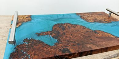 Carribean blue epoxy resin and rich wood burl with interesting grains in a serving tray.