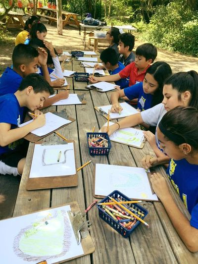 A group of children sitting outside on picnic tables and working a project using colors and pencils.