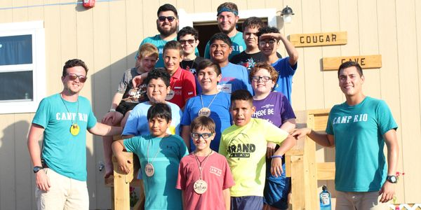 Two male summer counselors posing for a photo with a group of male campers in front of a cabin.