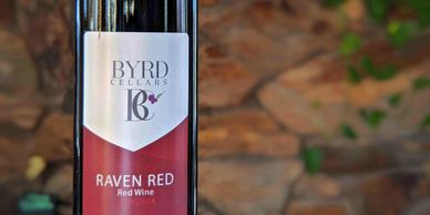 Byrd Cellars Raven red wine bottle in front of stone wall