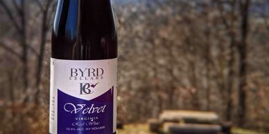bottle of Byrd Cellars velvet red wine on back porch railing overlooking the valley