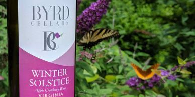 bottle of Byrd Cellars winter solstice wine with butterfly bush in background