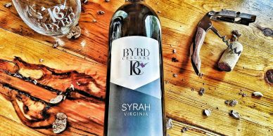 bottle of Byrd Cellars Syrah laying on table with Corkscrew, cork, and Empty Glass