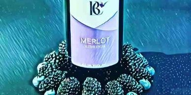 bottle of Byrd Cellars Merlot with blueberries and blackberries around bottom
