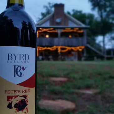 Bottle Of Byrd Cellars Pete's Red wine with the tasting room in the background, near dusk