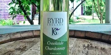 bottle of Byrd Cellars Creekside Chardonnay on wine barrel outside