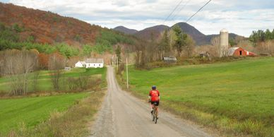 fall foliage on the mountains as a bicycle rider in red bikes away from the camera on a gravel road