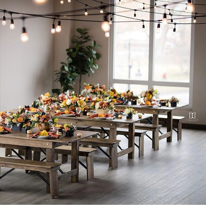 Image of event space with wood farm tables and floral centerpieces.