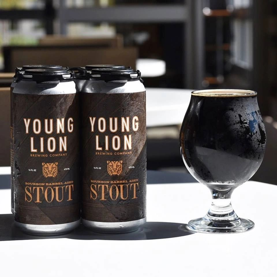 YLBC 4 pack cans of Bourbon Barrel Stout with a poured glass of stout next to it.