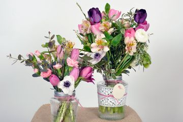 Two jars with pink and white floral displays