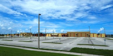 The Viera High School building with the parking lot in front.