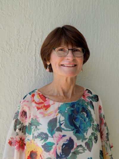 Photo of Colleen wearing a floral blouse.  Colleen has short brown hair with bangs & wears glasses.