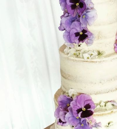 close up of a 3 tier semi-naked wedding cake decorated with fresh edible pansies and violas
