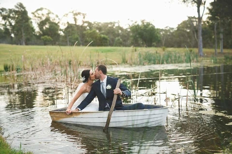 Happily married couple kissing on a row boat.