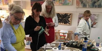 a group participating in an encaustic workshop
