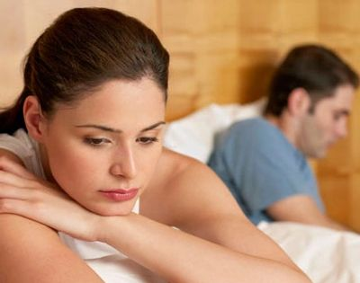 Couple in bed turning away from on another feeling upset