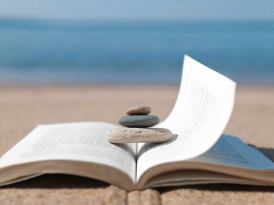 Book with zen rocks on the top of it on a sandy beach.