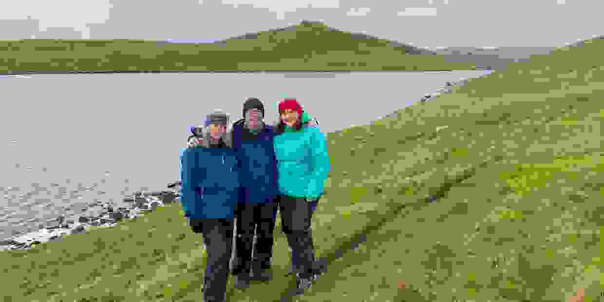 A tour group of three people pose for a photo on a grassy slope, with a loch behind and a hill crown