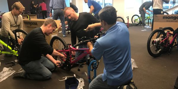 Bospar CEO and workers building bicycles to donate