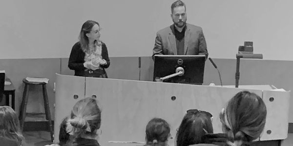 A woman and a man stand in front of a lecture hall delivering a speech. The woman holds a fidget toy