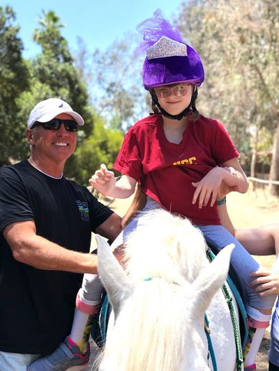 Young girl riding Bella the therapy pony for physical therapy treatment session using hippotherapy