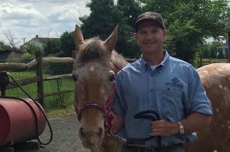 male owner standing with appaloosa mare