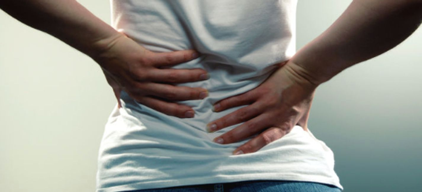 A woman in a white t-shirt holds her lower back in pain
